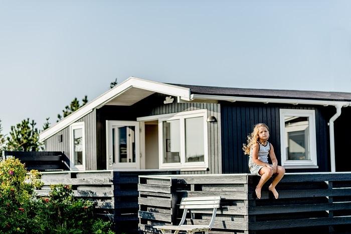 Younger Nordic girl with long, brown hair is sitting on a wooden fence surrounding a Danish summer house. Yngre nordisk pige med langt, brunt hår sidder på et hegn af træ ved et dansk sommerhus.