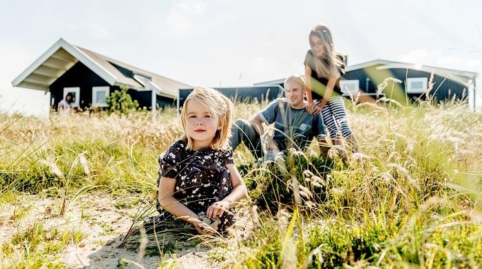 Father and daughters playing in the dunes and grass outside summer cabins in Thy, Denmark. Far og døtre som leger i klitterne og græsset udenfor sommerhuse i Thy, Danmark.